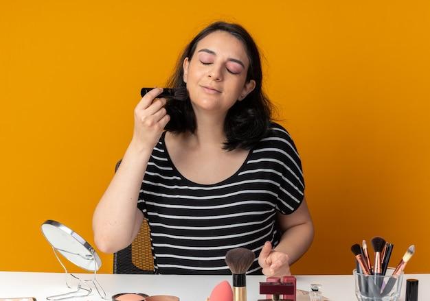 Blij met gesloten ogen zit een mooi meisje aan tafel met make-uptools die poederblush aanbrengen met een borstel geïsoleerd op een oranje muur