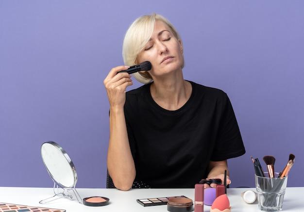 Blij met gesloten ogen zit een mooi meisje aan tafel met make-uptools die poederblush toepassen met poederborstel geïsoleerd op blauwe muur