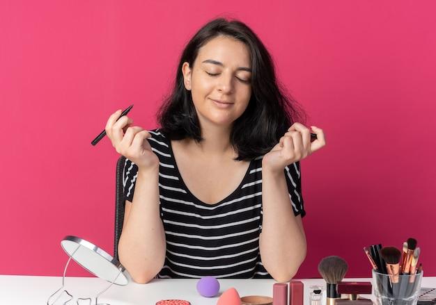 Blij met gesloten ogen zit een mooi meisje aan tafel met make-uptools met eyeliner geïsoleerd op een roze muur