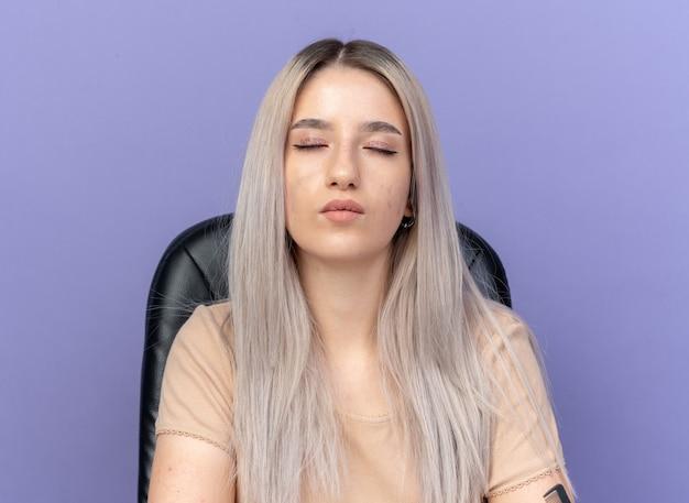 Blij met gesloten ogen zit jong mooi meisje aan tafel met make-up tools geïsoleerd op blauwe muur