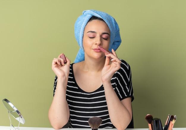 Blij met gesloten ogen zit jong mooi meisje aan tafel met make-up tools gewikkeld haar in handdoek houden en snuiven lippenstift geïsoleerd op olijfgroene muur