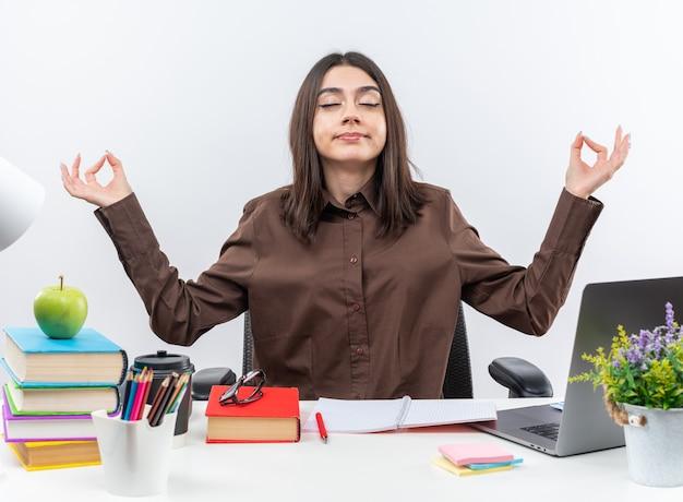 Blij met gesloten ogen zit jonge schoolvrouw aan tafel met schoolgereedschap en doet meditatiegebaar