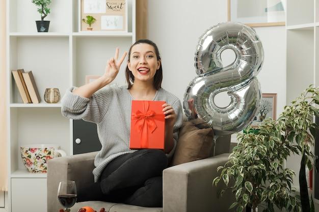 Blij met tong en vredesgebaar mooi meisje op gelukkige vrouwendag met cadeau zittend op fauteuil in woonkamer