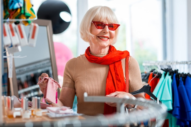 Blij met winkelcollectie. portret van vrolijke bejaarde vrouw wegkijken door rode zonnebril terwijl het kiezen van een hoofdband voor het matchen van haar jurk