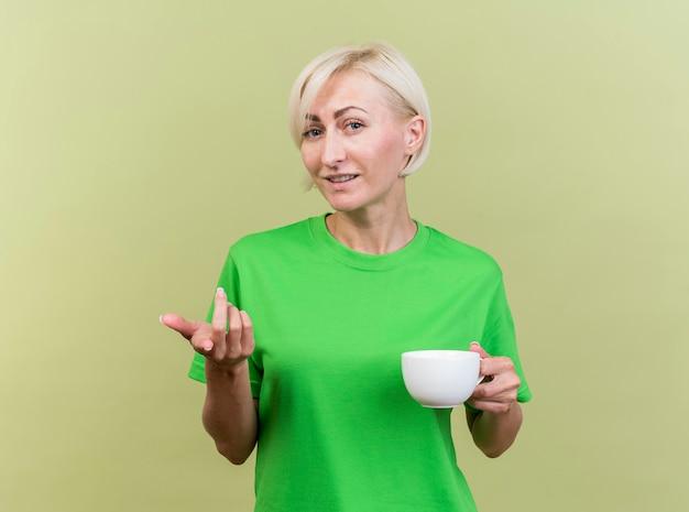 Blij middelbare leeftijd blonde slavische vrouw kijken en wijzend op camera met kopje thee in de hand geïsoleerd op olijfgroene achtergrond met kopie ruimte