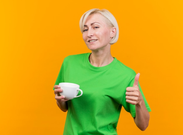 Blij middelbare leeftijd blonde slavische vrouw met kopje thee kijken camera weergegeven: duim omhoog geïsoleerd op gele achtergrond met kopie ruimte