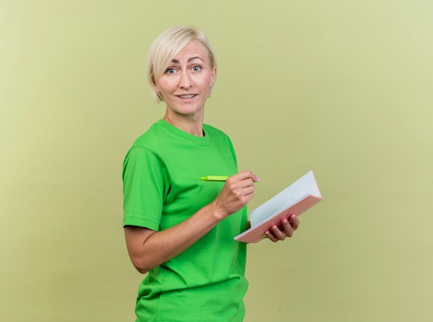 Blij middelbare leeftijd blonde slavische vrouw permanent in profiel te bekijken kijken naar camera met pen en notitieblok geïsoleerd op olijfgroene achtergrond met kopie ruimte