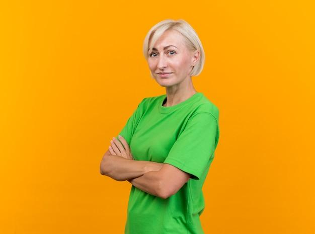 Blij middelbare leeftijd blonde slavische vrouw permanent in profiel te bekijken met gesloten houding kijken naar camera geïsoleerd op gele achtergrond met kopie ruimte