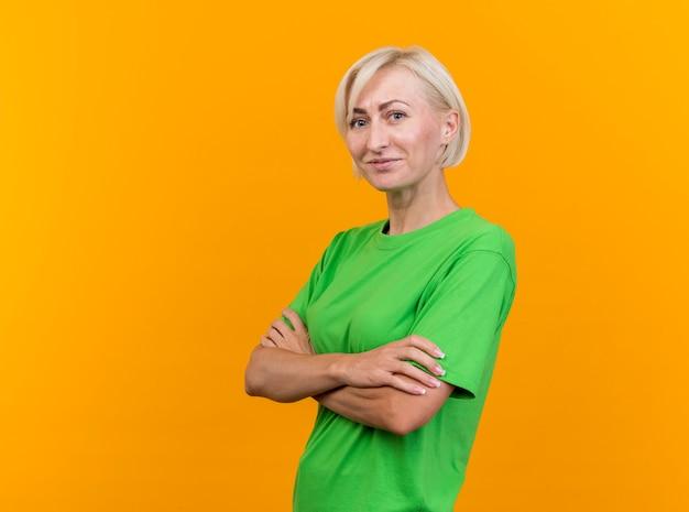 Blij middelbare leeftijd blonde slavische vrouw stond met gesloten houding in profielweergave kijken naar camera geïsoleerd op gele achtergrond met kopie ruimte