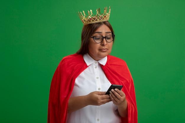 Blij middelbare leeftijd superheld vrouwtje dragen kroon met bril houden en kijken naar telefoon geïsoleerd op groene achtergrond