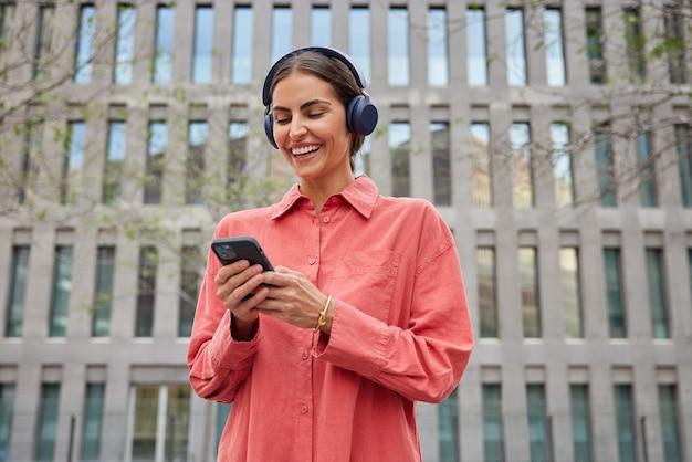 Blij millennial meisje met donker haar geniet van vrije tijd luistert muziek afspeellijst maakt gebruik van moderne smartphone draadloze hoofdtelefoon heeft stadswandeling gekleed in rood shirt poses tegen modern gebouw