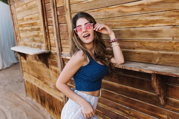 Blij modieus meisje in zonnebril dromerig poseren, leunend op de muur van een houten gebouw.