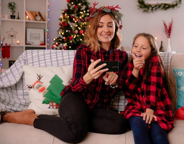 Blij moeder en dochter kijken naar iets op telefoon zittend op de bank en genieten van kersttijd thuis