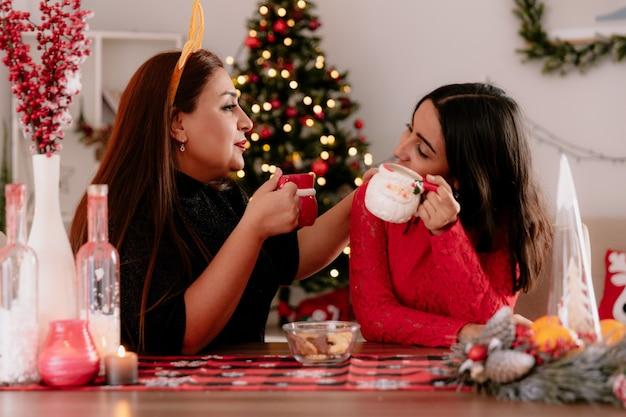 Blij moeder met rendieren hoofdband en dochter kijken elkaar bedrijf kopjes zittend aan tafel genieten van de kersttijd thuis