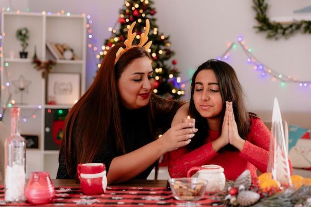 Blij moeder met rendieren hoofdband houdt en kaars kijkt met haar dochter zittend aan tafel genieten van de kersttijd thuis