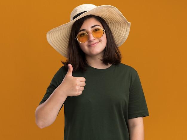 Blij, mooi blank meisje in zonnebril en met strandhoed die omhoog wijst, geïsoleerd op een oranje muur met kopieerruimte