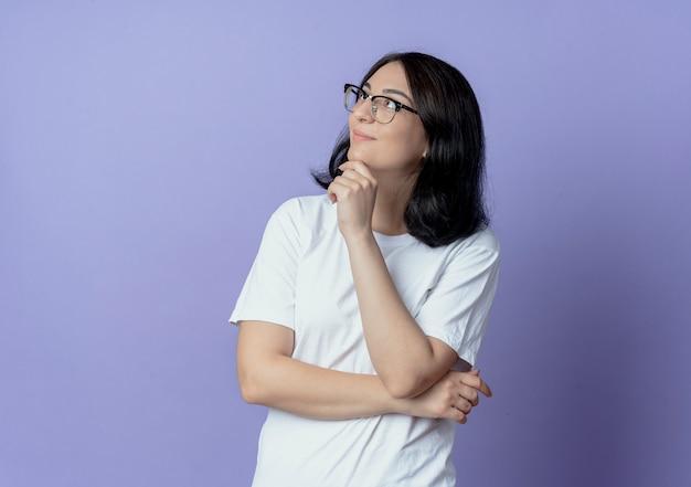 Blij, mooi blank meisje met een bril die handen onder de elleboog en op de kin zet en naar de zijkant kijkt