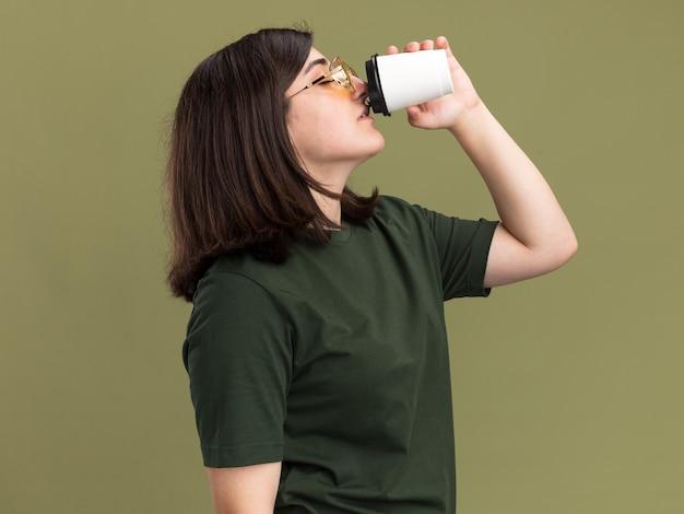 Blij, mooi blank meisje met zonnebril staat zijwaarts te drinken uit een papieren bekertje