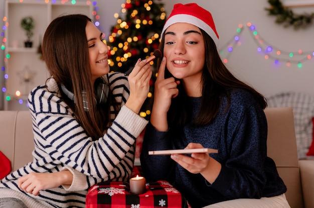 Blij mooi jong meisje doet make-up van haar vriend met kerstmuts zittend op een fauteuil en thuis genietend van kersttijd