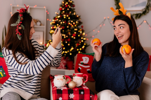 Blij mooi jong meisje met hulstkrans maakt foto van haar vriend die sinaasappels vasthoudt terwijl ze op een leunstoel zit en thuis geniet van de kersttijd