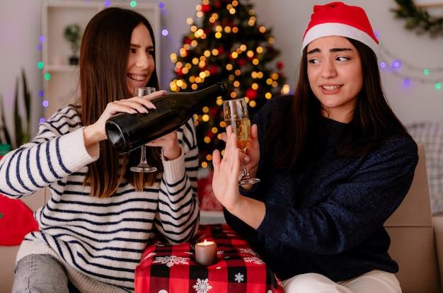 Blij mooi jong meisje met kerstmuts houdt glas champagne en gebaren stopbord naar haar vriend fles champagne zittend op een stoel te houden en thuis te genieten van de kersttijd