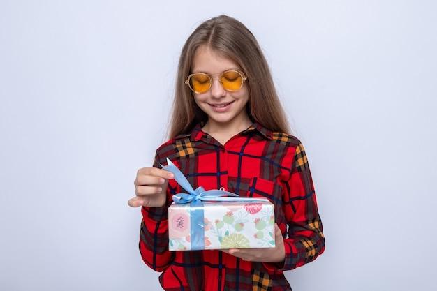 Blij mooi klein meisje met een rood shirt en een bril die het heden vasthoudt en bekijkt