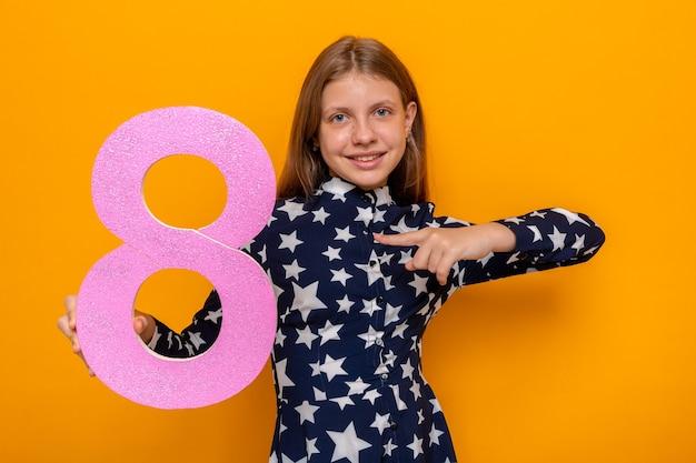 Blij mooi meisje op gelukkige vrouwendag en wijst naar nummer acht