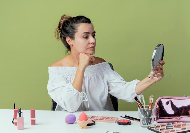 Blij mooi meisje zit aan tafel met make-up tools hand op kin houden en kijken naar spiegel geïsoleerd op groene muur