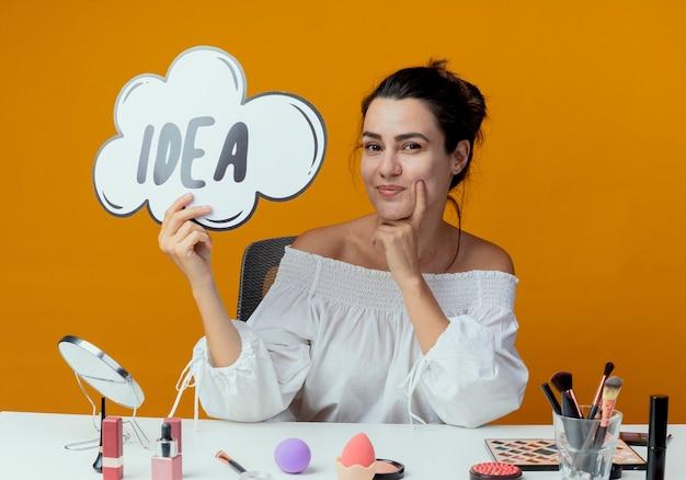 Blij mooi meisje zit aan tafel met make-up tools houden idee teken kijken geïsoleerd op oranje muur
