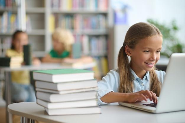 Blij mooi scholier typen op de laptop