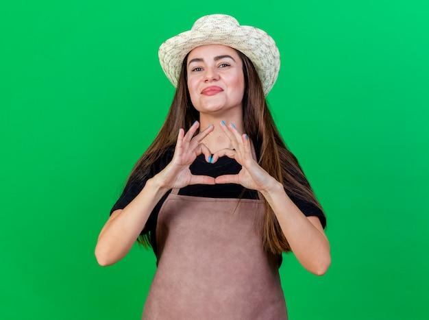 Blij mooi tuinman meisje in uniform dragen tuinieren hoed weergegeven: hart gebaar geïsoleerd op groene achtergrond