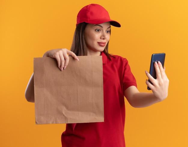 Blij mooie bezorger in uniform houdt papieren pakket vast en kijkt naar telefoon geïsoleerd op oranje muur met kopieerruimte