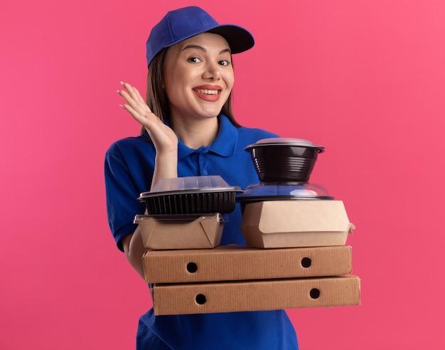Blij mooie bezorger in uniform staat met opgeheven hand en houdt voedselpakket en containers op pizzadozen
