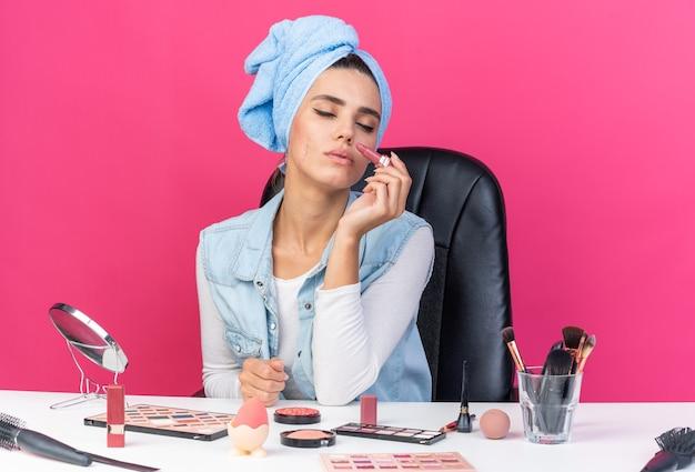Blij mooie blanke vrouw met gewikkeld haar in een handdoek zittend met gesloten ogen aan tafel met make-up tools met lippenstift