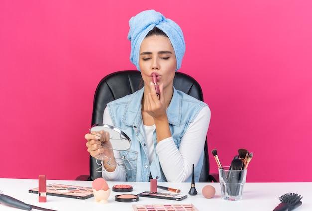 Blij mooie blanke vrouw met gewikkeld haar in handdoek zittend aan tafel met make-up tools spiegel te houden en lippenstift geïsoleerd op roze muur met kopie ruimte toe te passen