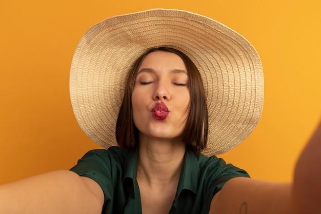 Blij mooie blanke vrouw met strandhoed beweert camera te kussen die selfie op sinaasappel neemt