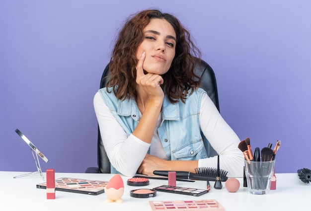 Blij mooie blanke vrouw zittend aan tafel met make-up tools hand op haar kin op zoek geïsoleerd op paarse muur met kopieerruimte