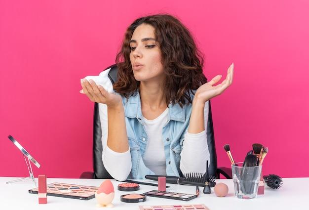 Blij mooie blanke vrouw zittend aan tafel met make-up tools houden en kijken naar haarmousse geïsoleerd op roze muur met kopieerruimte