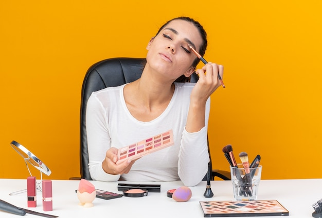 Blij mooie blanke vrouw zittend aan tafel met make-up tools houden oogschaduw palet en het toepassen van oogschaduw geïsoleerd op oranje muur met kopie ruimte