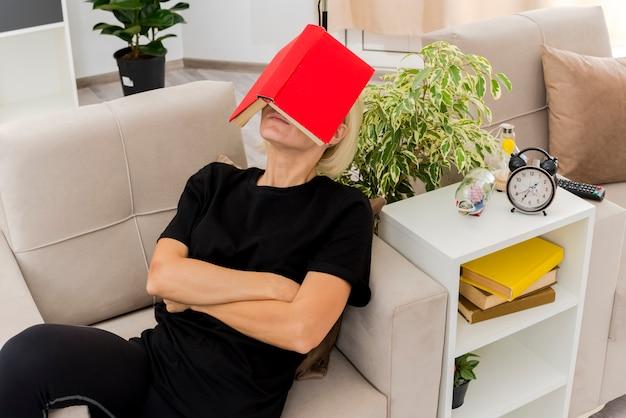Blij mooie blonde russische vrouw liggend op een leunstoel boek op het gezicht houden en de armen kruisen in de woonkamer
