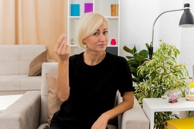 Blij mooie blonde russische vrouw zit op fauteuil gebaren geld hand teken in de woonkamer