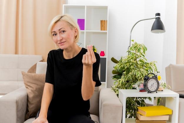 Blij mooie blonde russische vrouw zit op fauteuil gebaren geld handteken in de woonkamer