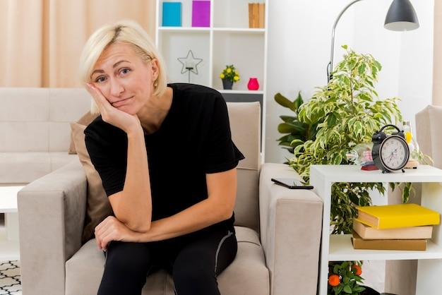 Blij mooie blonde russische vrouw zit op fauteuil hand op kin te kijken naar camera in de woonkamer