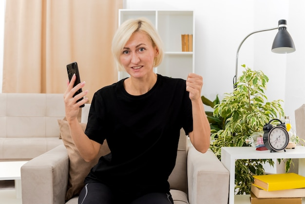 Blij mooie blonde russische vrouw zit op fauteuil vuist houden en telefoon in de woonkamer te houden