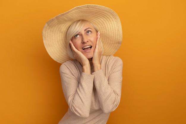 Blij mooie blonde slavische vrouw met strandhoed legt handen op gezicht en kijkt op oranje