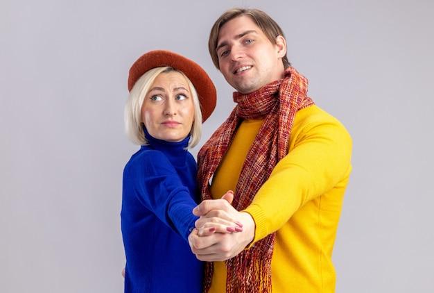 Blij mooie blonde vrouw met baret dansen met knappe slavische man geïsoleerd op een witte muur met kopie ruimte