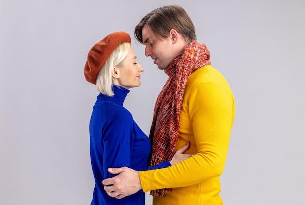 Blij mooie blonde vrouw met baret en knappe slavische man met sjaal om zijn nek kijken elkaar aan op valentijnsdag