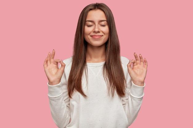 Blij mooie brunette poseren tegen de roze muur