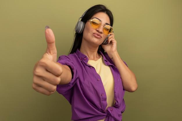 Blij mooie brunette vrouw in zonnebril met koptelefoon thumbs up geïsoleerd op olijfgroene muur