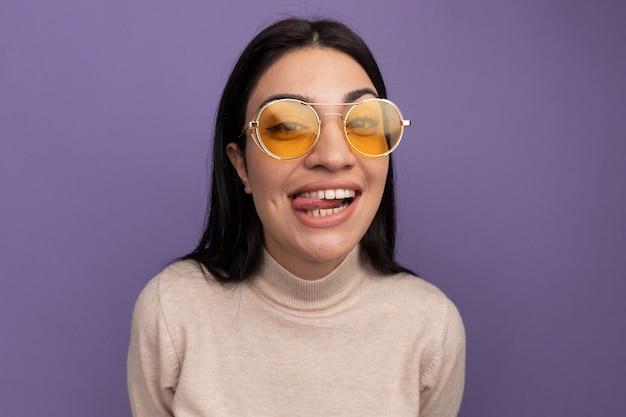 Blij mooie brunette vrouw in zonnebril steekt tong uit en kijkt naar voorzijde geïsoleerd op paarse muur